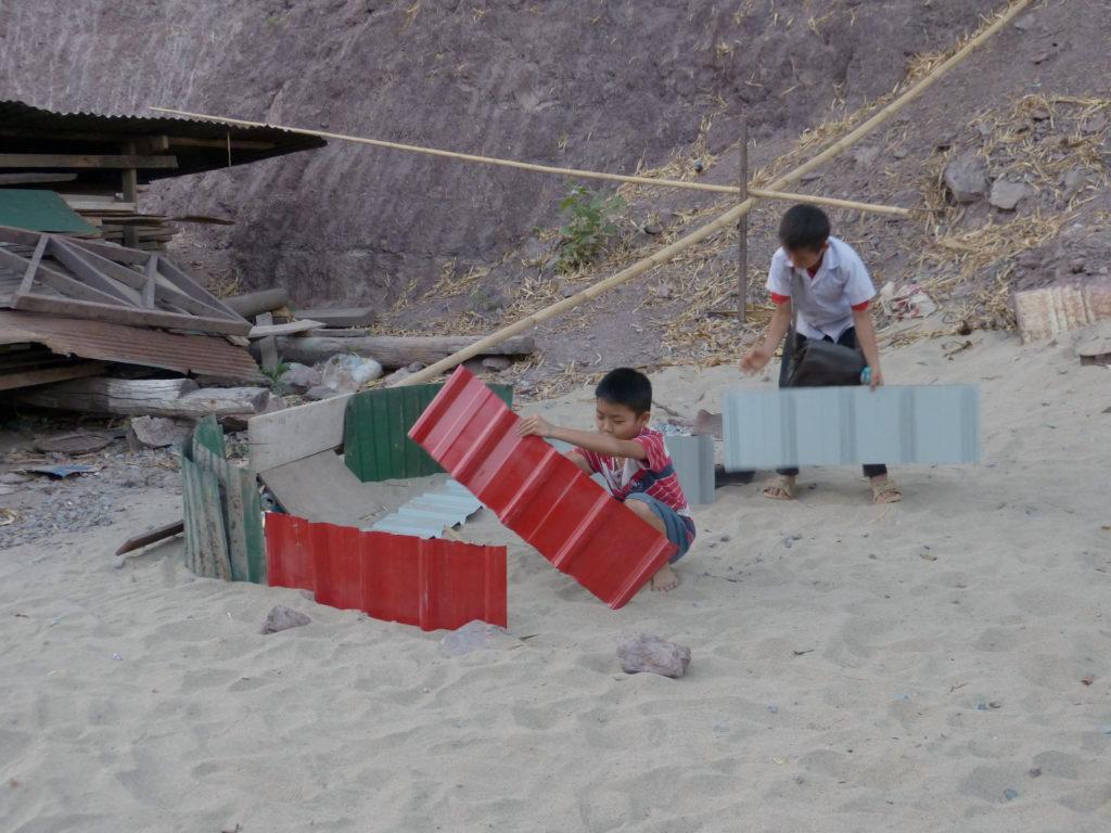 Construire, un jeu, au bord d'une route. Laos, 2016 (Habitant)